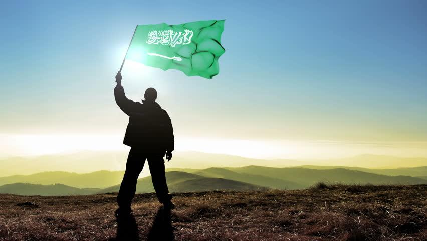 Successful silhouette man winner waving Saudi Arabia flag on top of the mountain peak, 4k cinemagraph