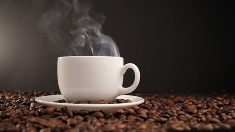 cup with hot drink on roasted coffee beans. dolly shot