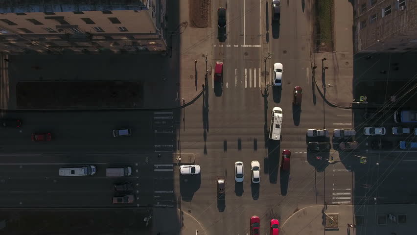 Camera rotating above crossroads in the city, cars drive through the solar part of the road, aerial view. St. Petersburg, Russia | Shutterstock HD Video #15905017