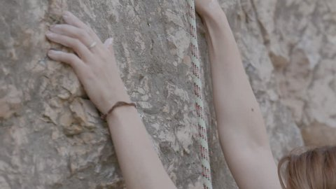 A female rock climber climbs up a rock. Learning to climb