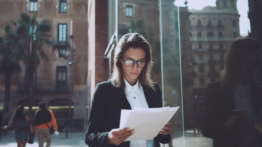 Young professional businesswoman or female manager looking concentrated on documents, outdoors | Shutterstock HD Video #15911686
