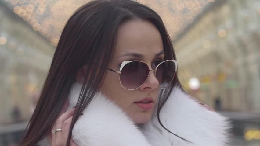 Fashion photo of beautiful young  woman with sunglasses. Model looking at camera. City lifestyle. Female fashion. Closeup portrait. Beautiful reflection background