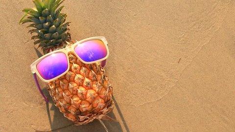 pineapple in sunglasses on sand beach.