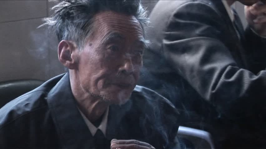 BEIJING, CHINA - CIRCA 2009: An old man smokes a cigarette and looks at the camera circa 2009 in Beijing .