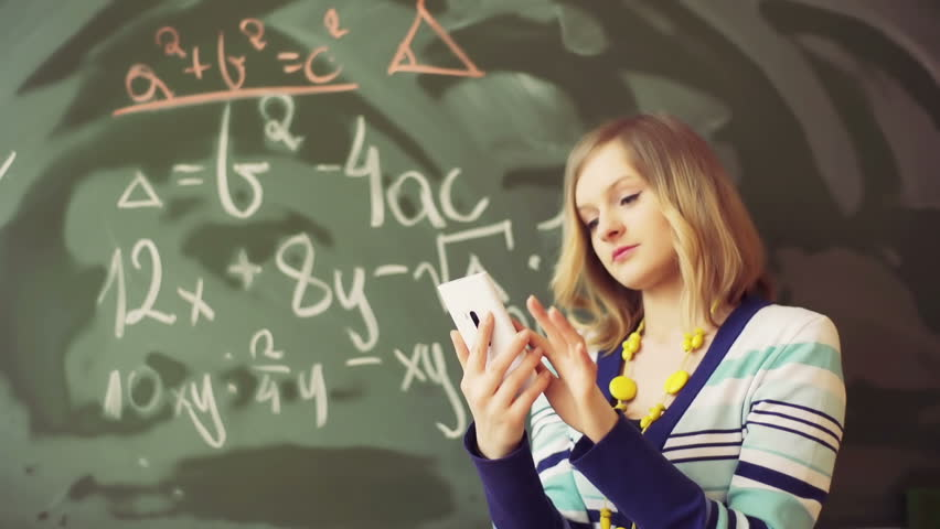 Math teacher standing in the class and texting on smartphone - HD stock  video clip
