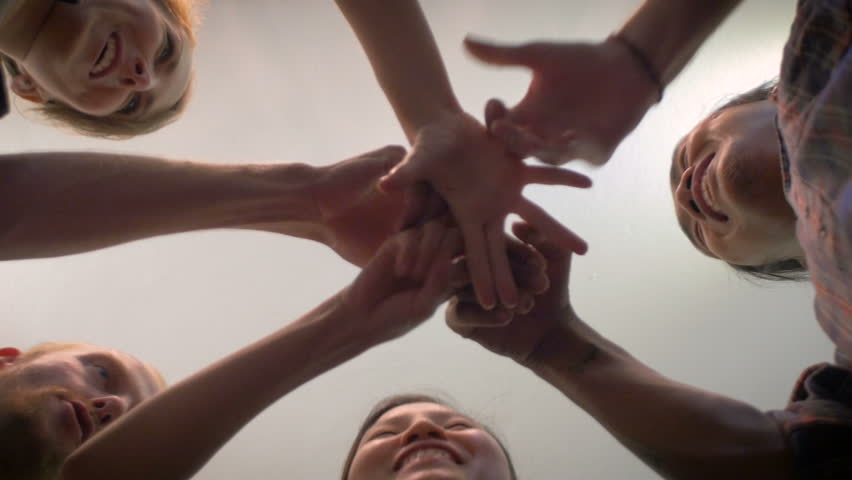 A group of 5 young millennials do an exploding fist bump with their hands together in the center of a circle and then cheer in a celebration of a successful event - low angle shot.