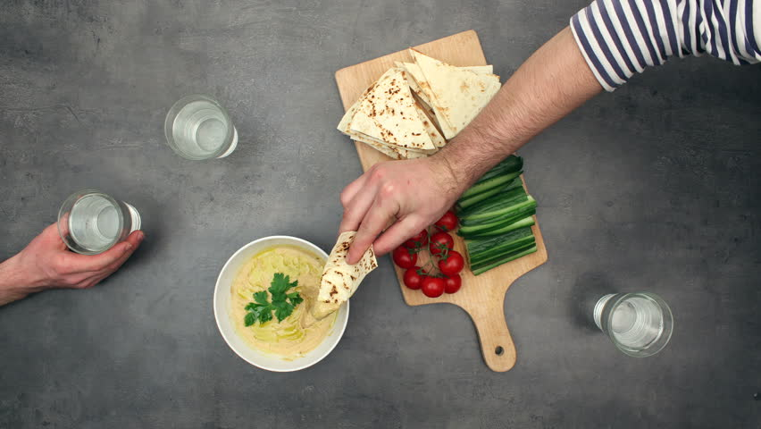 Preparing Hummus / Houmous - oriental recipe (stop motion animation). Top view on ingredients and timelapse of eating with pita bread and fresh vegetables.