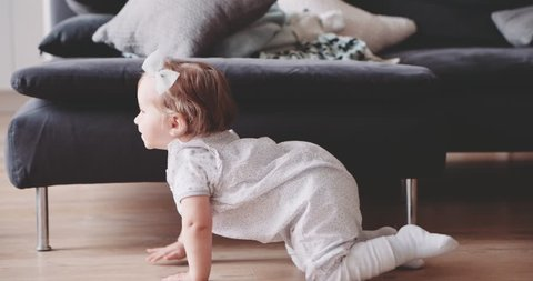 Baby is crawling at home, Slow Motion 120 fps, 4K DSi. Cute little baby girl crawling and smiling at the floor in a cozy sunlit room, baby milestone, toddler, 1 year old. Happy childhood. Cinematic