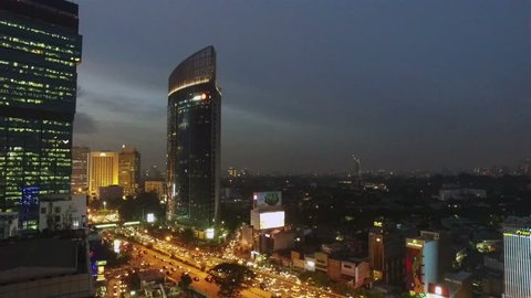 Panned view to the left of Jakarta business district, with various bank HQ and luxury hotels, at night around Plaza Indonesia along Sudirman avenue in Indonesia capital city.