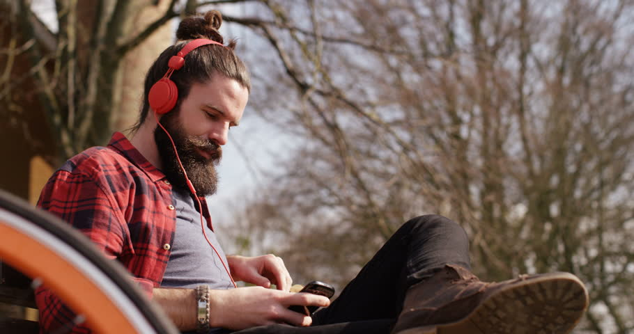 4k, Shot of a happy young man listening to music on headphones in the park | Shutterstock HD Video #16003666