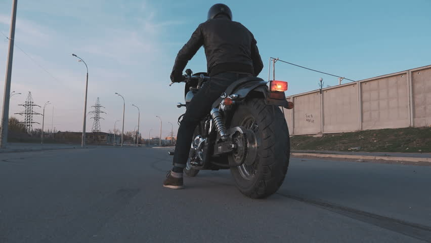 Young man doing a tire burnout on motorcycle on the road at sunset, slow motion, steady come