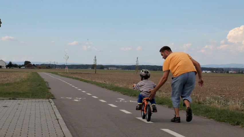 The father teaches a little boy riding a bike.