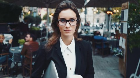 Attractive young businesswoman wearing glasses and drinking coffee to go, female student holding laptop and drinking coffee at cafeteria, slow motion