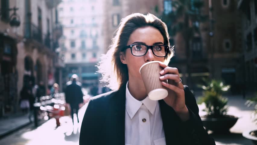 Portrait of young attractive businesswoman drinking coffee to go on a break and using modern smartphone outdoors, sunshine, slow motion