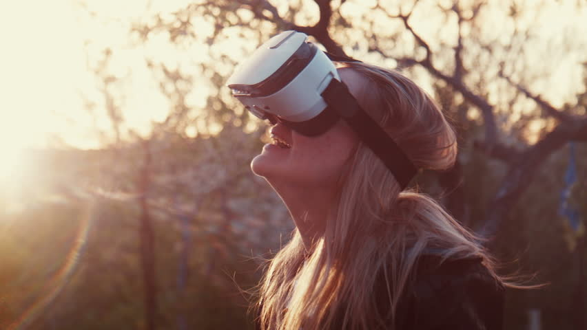 Young blonde insert the smartphone in a virtual reality helmet,  puts on shes head and looks 360 degrees video or playing a game