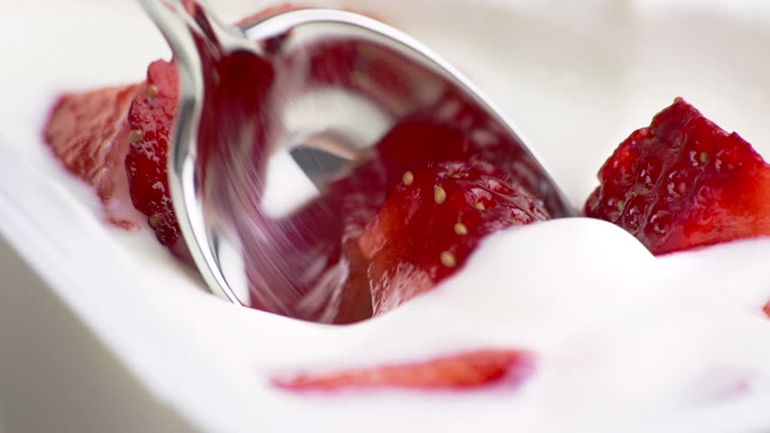 close-up of healthy strawberry and white yogurt on the spoon, concept of healthy food nutrition