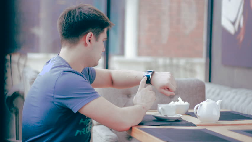 Handsome man with smartwatch sitting in cafe in city. | Shutterstock HD Video #16071304