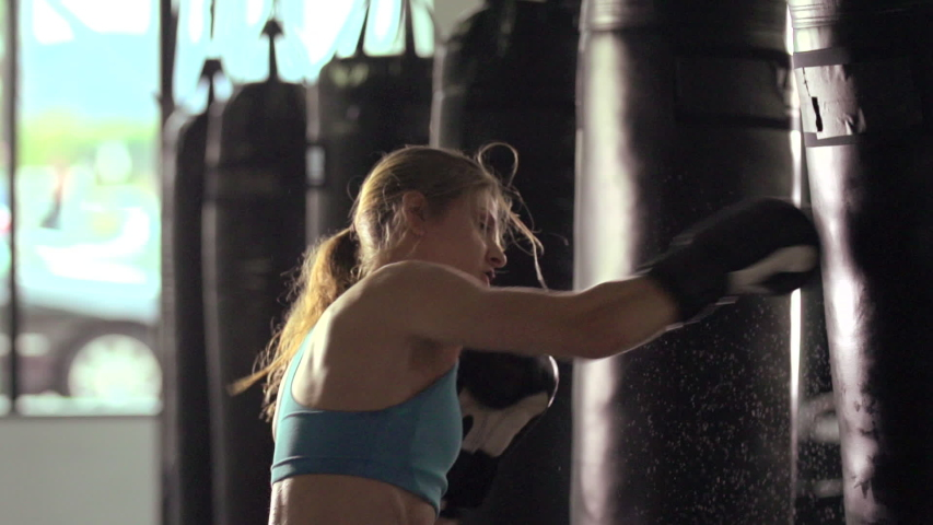 Woman does Muay Thai kickboxing training at the gym. - Super Slow Motion - Model Released - filmed at 240 fps
