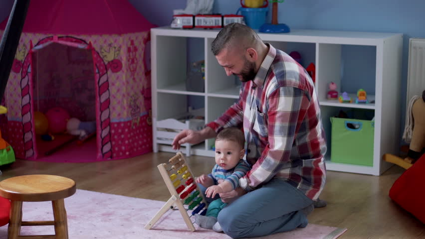 Dad counts on abacus with his kid in babyroom and talking on the cell