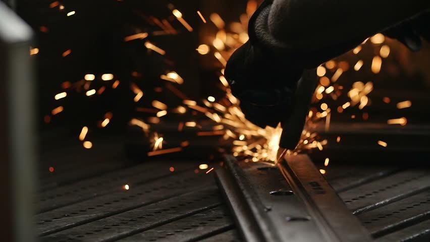 Worker using industrial grinder on metal rail track parts in industrial workshop warehouse.