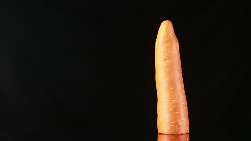 woman fondles carrots on a black background. erotic games