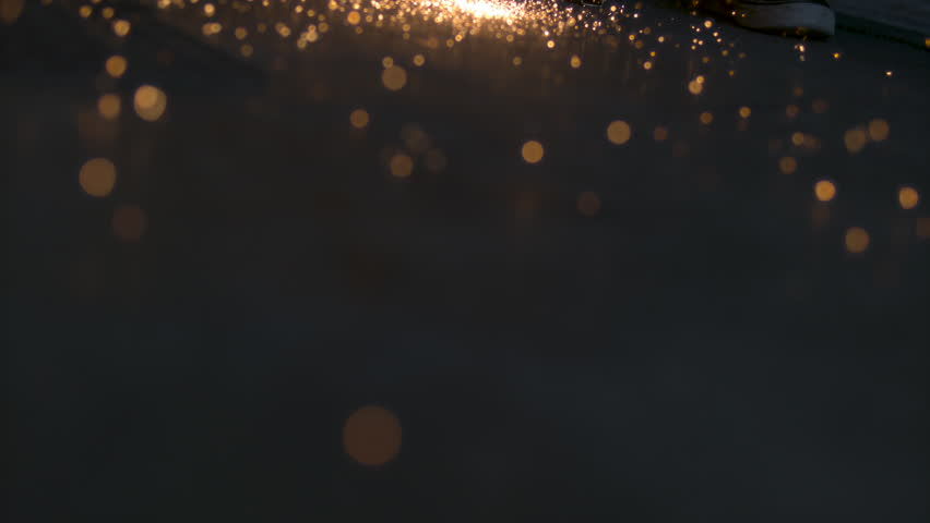 Sparks from an industrial grinder fall and bounce on the ground of a workshop as we FLY across and up in SLOW MOTION #16130746