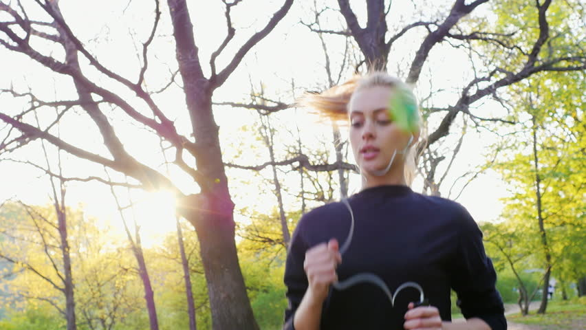 Jogging in the forest on the background of the setting sun.    Shutterstock HD Video #16132696