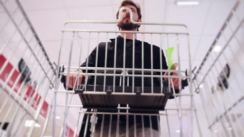 Man With Shopping List And Supermarket Cart. Man with a shopping list in hands and a trolley walking in a supermarket | Shutterstock HD Video #16143916