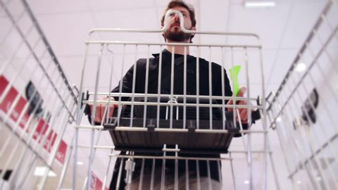 Man With Shopping List And Supermarket Cart. Man with a shopping list in hands and a trolley walking in a supermarket