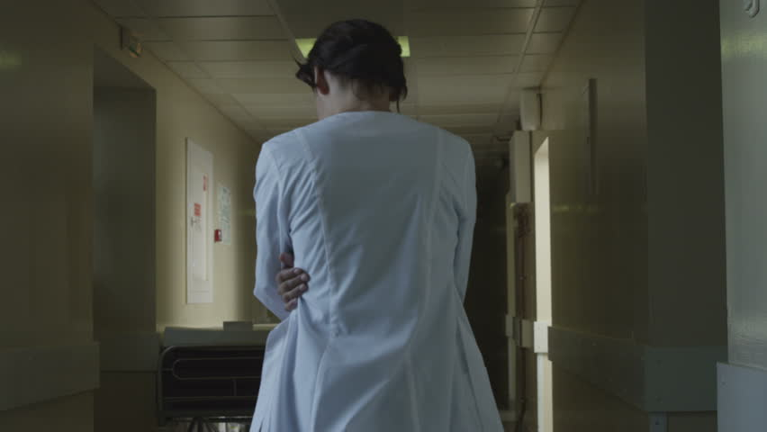 Confused woman doctor in hospital hear something in corridor