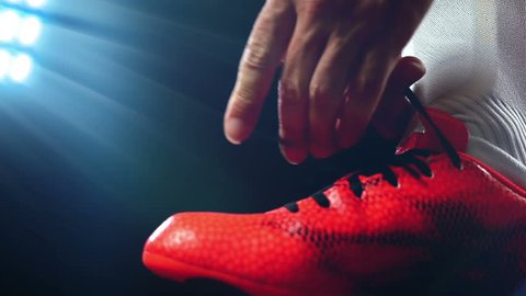 Football, soccer game. Professional footballer buckle his red shoes, slow motion