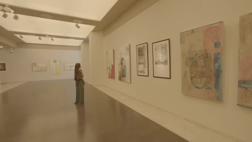 Bahrain National Museum, Bahrain - 2013 - Tracking shot showing paintings displayed on a wall in one of the museum's galleries. A Bahraini woman is looking at the paintings.