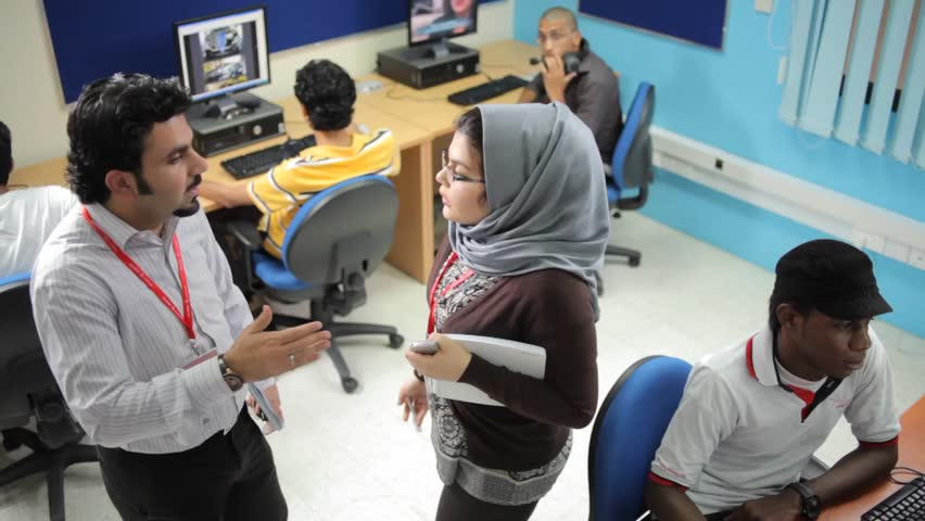 Bahrain - circa 2011 - Bird's eye shot of two teachers (a man and a veiled woman) in conversation in a computer lab. Male students work on computers around the teachers.