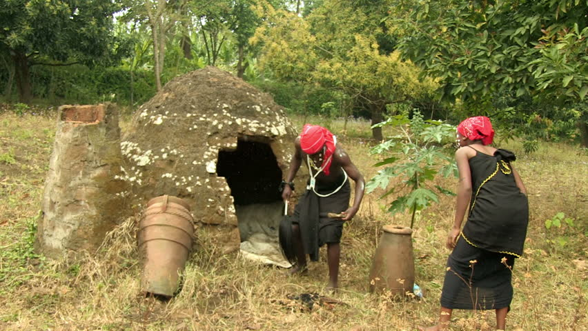 Arusha rural district, Tanzania - March, 2015: A male and female witches performing witchcraft rituals and spells around a mud hut