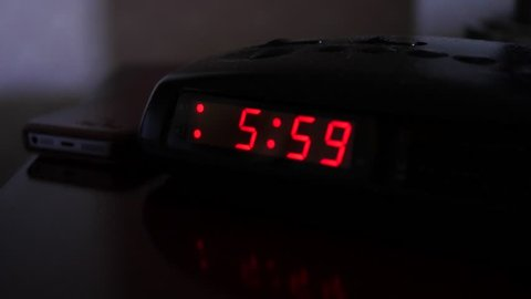 A digital alarm clock turns to six o'clock