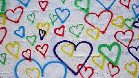 HEARTS.  COLORFUL AND HAND PAINTED ON A WHITE WALL.
