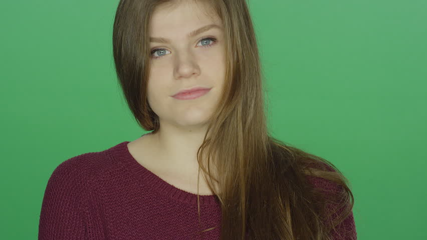 Young brunette woman runs her fingers through her hair and poses, on a green screen studio background | Shutterstock HD Video #16253506