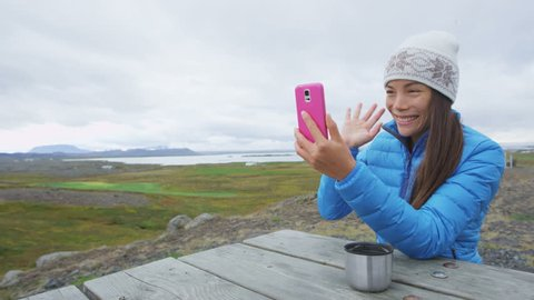 Video chat conversation - Woman on smart phone talking in nature outdoor using smartphone app. Girl waving saying hello saying hi to person on phone. Active lifestyle on Iceland.