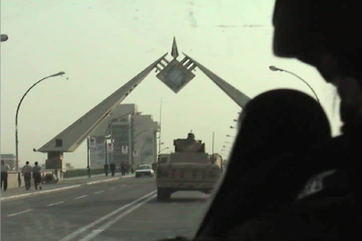 POV from a U S army convoy moving under the victory arch in central Baghdad during the Iraq War.