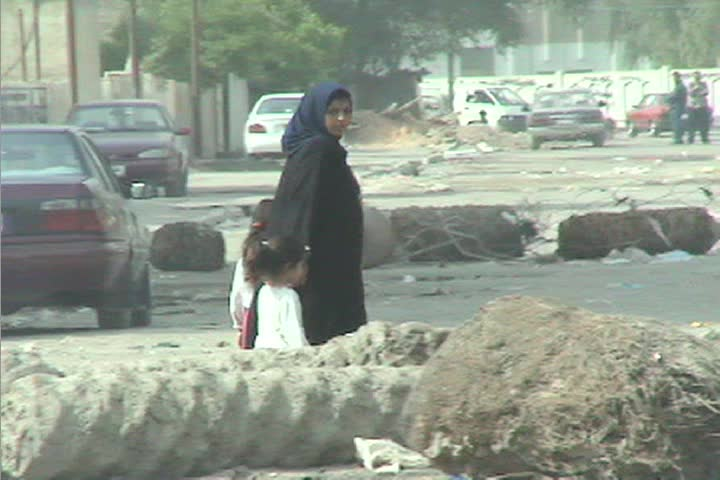 BAGHDAD, IRAQ - CIRCA 2009: A veiled woman leads her children through the streets of Baghdad during the Iraq war.