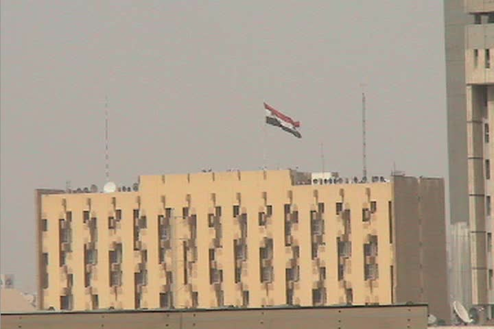 The Iraqi flag flies high above a public building in downtown Baghdad Iraq.