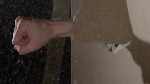 Smashing through Drywall in slow motion - fist coming through the wall