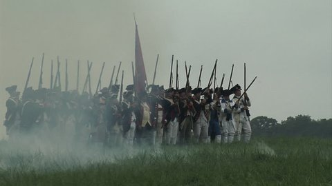 VIRGINIA - OCTOBER 2014 - Reenactment, large-scale, epic American Revolutionary War anniversary recreation -- in the middle of battle.  Cannons, Cavalry, British Redcoats and Continental Soldiers.