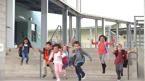 Young school kids jumping down steps as they leave school