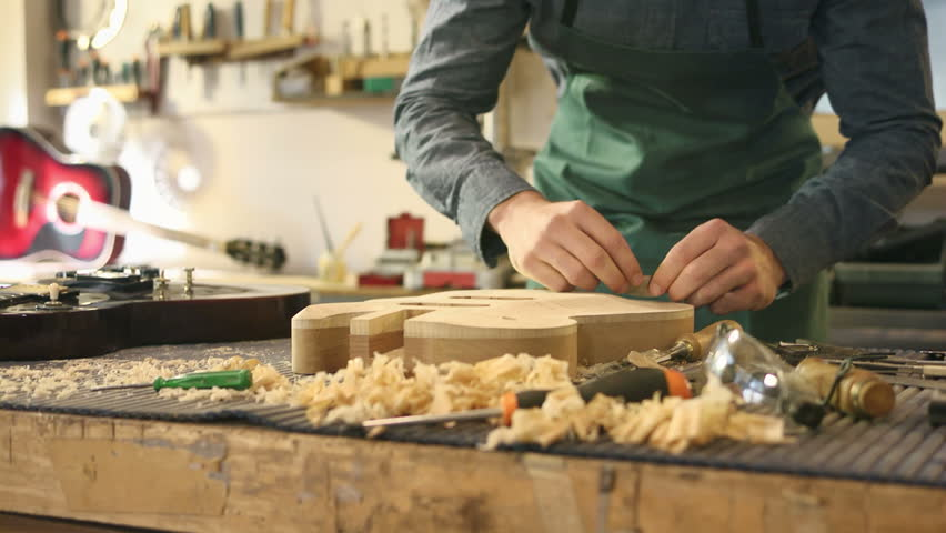 People and art, man working as artisan in italian workshop with guitars and musical instruments, smoothing guitar body