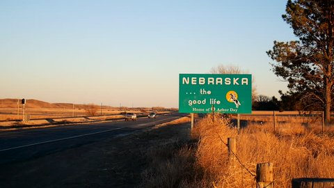 NEBRASKA, USA - 28 JAN 2014: View of Nebraska welcome road sign with vehicles passing by