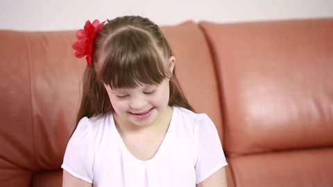 Emotions of a little girl with Down syndrome. disabled girl laughs