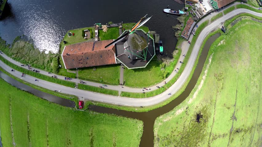 Aerial top down view Zaanse Schans one of most popular tourist attractions of Netherlands Holland near Amsterdam beautiful drone footage moving up looking down on windmills mills renewable energy 4k