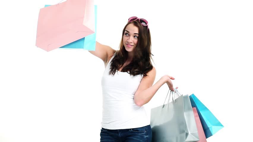 Joyful teenager holding shopping bags and laughing and smiling - isolated on white
