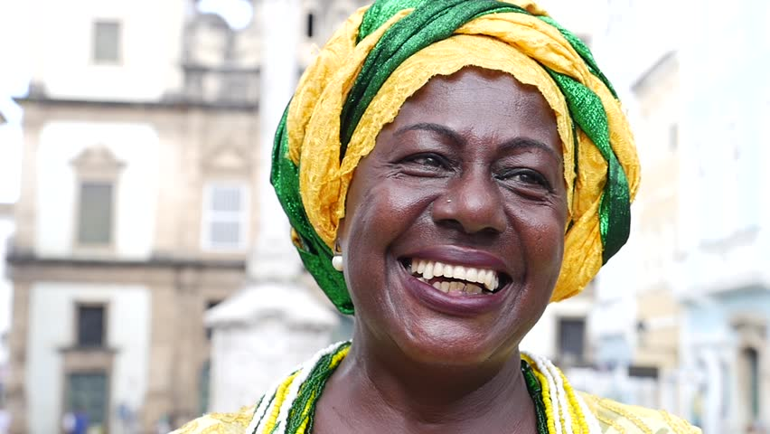 Brazilian woman of African descent, smiling, dressed in traditional Baiana attire in Pelourinho, Salvador, Bahia, Brazil